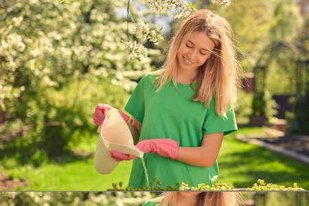 Cute happy teen girl watering flowers, in a wooden pot, from a watering can, in her home garden. Reklamní fotografie
