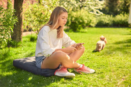 A cool girl student is sitting in the yard with a dog on the lawn and uses a smartphone to order clothes online.