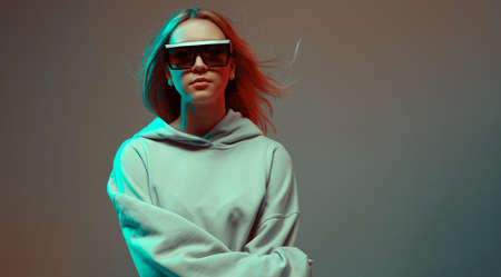 Portrait of a stylish young girl, cool posing in a hoodie, sunglasses and with developing hair, on a neon background.