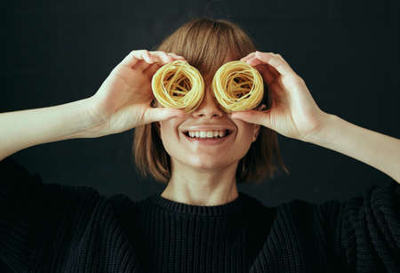 Portrait of a happy girl closes her eyes with nests of spaghetti macaroni with a smile on a black background.