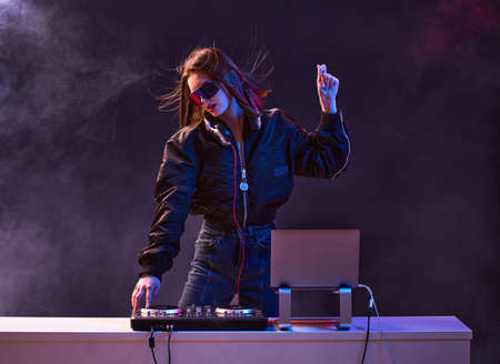 Stylish girl DJ in glasses headphones and a bomber mixes music dancing at a party in the neon light in the smoke . High quality photo