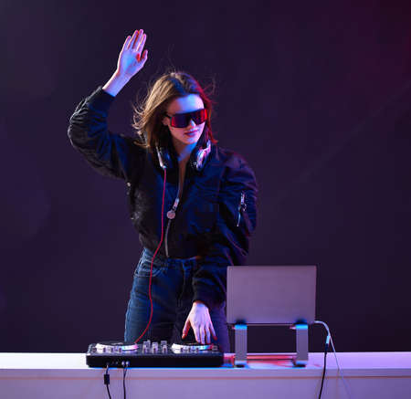 Stylish DJ girl with headphones and glasses on the bomber jacket mixes the music at the party and neon lights.