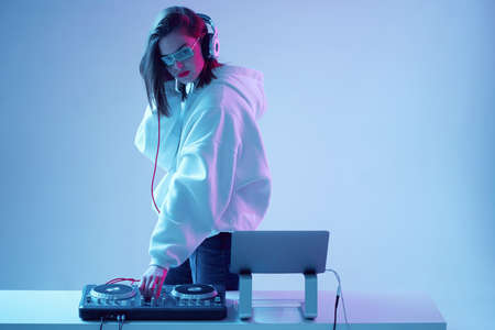 Cool young girl DJ mixes music on a mixing console and laptop, in stylish clothes, glasses on a neon background.