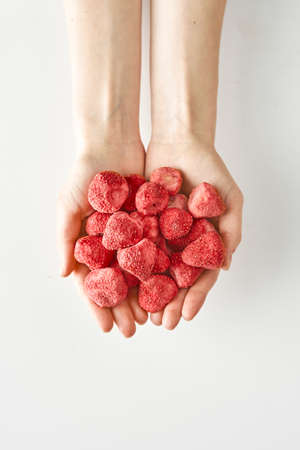 Dry strawberry in hands isolated on white background, healthy food and lifestyle,100 calories portion of healthy snack