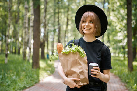 Young smiling girl in hat with vegetables and cup of coffee to go walking in park, photography for blog or advertising Archivio Fotografico