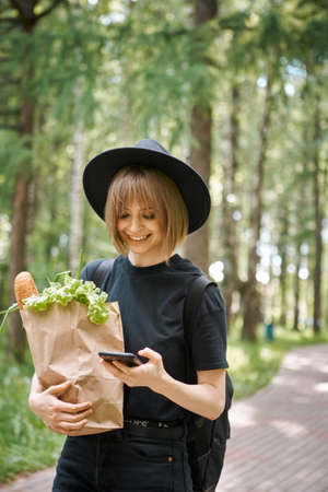 Young smiling girl with bag with vegetables and phone walking in park, photography for blog or advertising