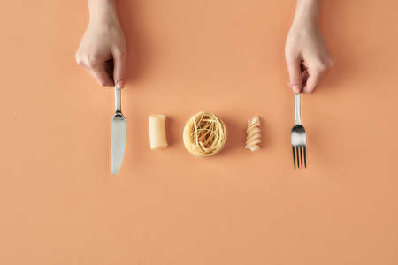Fettuccine, tortiglioni, fusilli pasta and hands with fork and knife, concept photography for food blog or advertising