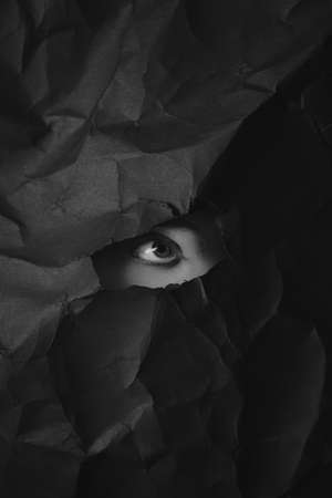 Woman's eye in hole in black crumpled paper background, black and white concept photography for blog or poster. High quality photo Stock fotó