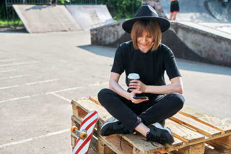 Pretty young girl blogger working on phone sitting on wooden pallet in skatepark with skateboard and cup coffee to go