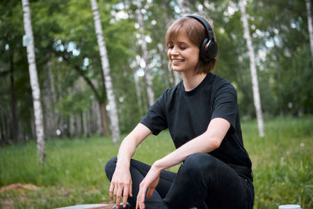 Pretty teen girl in wireless headphones listening to music and meditating in the park, photography for ad or blog