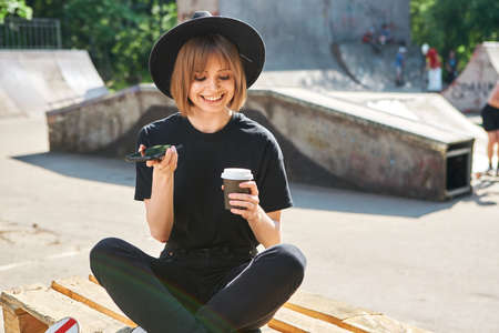 Pretty happy girl blogger communicate by phone sitting on wooden pallet in park with cup coffee to go