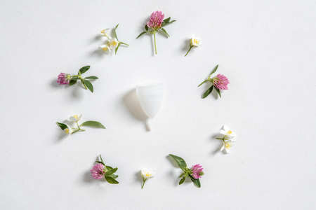 Menstrual cup eco-friendly reusable silicone and flowers isolated on a white background, photography for a womens blog
