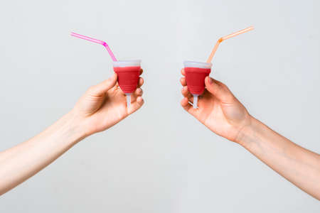 Menstrual cups eco friendly reusable and silicone in womens hands isolated on white background with a cocktail tubes