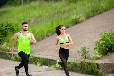 Athletic girl and man in stylish sportswear run in nature, photo for blog and ad of sport and healthy lifestyle Stock Photo