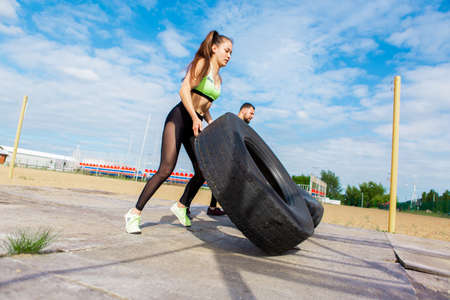Athletic girl and guy flipping tire in stylish sportswear, photography for blog or ad of sport and healthy lifestyle