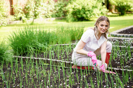 A young pretty girl in a shawl and rubber gloves is planting onions in her backyard garden on a Sunny summer day.