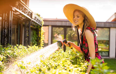 Pretty smiling girl in a hat watering plants with a garden hose in the garden in summer, photography for blog or ad