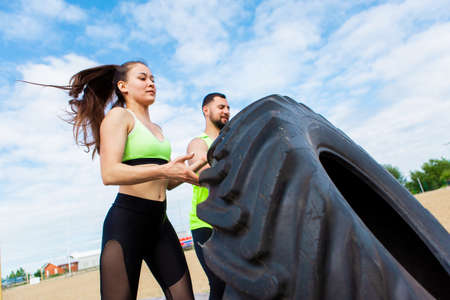 Athletic girl and guy push gym tire in stylish sportswear, photography for blog or ad of sport and healthy lifestyle