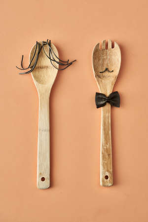Cartoon girl and man made up of farfalle pasta and wooden spoon, conceptual photography for food blog or ad. High quality photo