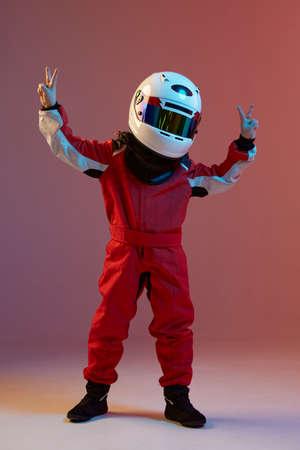 Cool boy child racer in helmet with raised hands with peace gesture, standing in neon light. Kart racing school poster