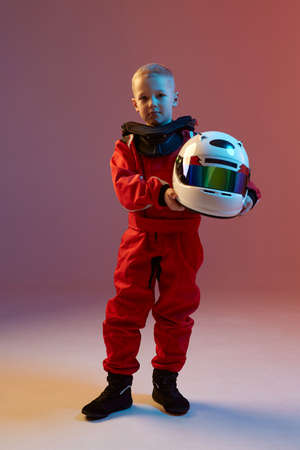 Cool boy child racer with helmet, standing in neon light. Kart racing school poster. Competition announcement Stockfoto