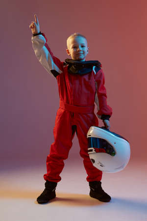 Boy child racer with helmet and his hand up, standing in neon light. Kart racing school poster. Competition announcement Stock Photo