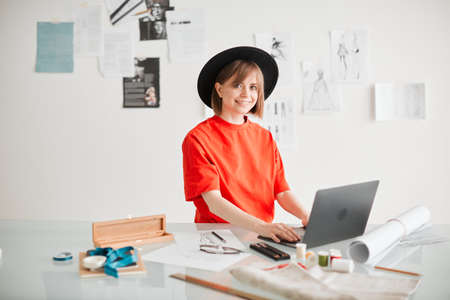Smiling girl fashion designer working in studio. Photography for blog or ad educational courses or clothing