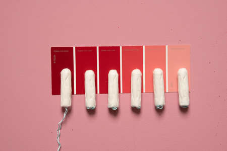 Soft white womens tampons on palette of shades of red. Close concept photography for a womens or feminist blog or ad