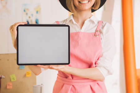 Close up of smiling pretty woman artist showing blank screen tablet. Cozy photography for ad or blog Stock Photo