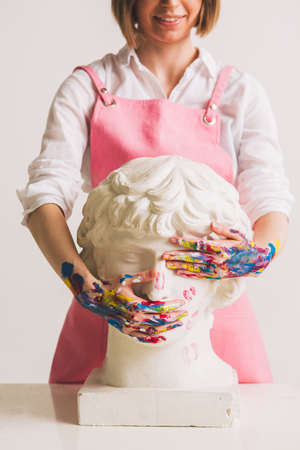Gypsum statue of Antinous head. Plaster statue in womans hands. Concept photography about art and gender