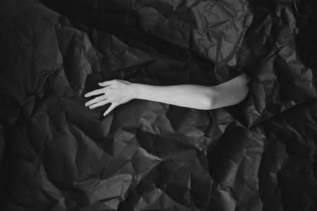 Womans hand comes out of hole in black crumpled paper, black and white concept photography for beauty blog or poster
