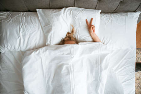 Young teen girl under blanket in white bed in bedroom with gesture V sign. Healthy sleep, sleep apps, lazy morning