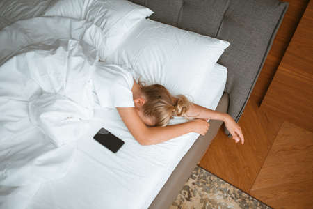 Young girl sleep with phone under blanket in white bed in bedroom. Healthy sleep, healthy sleep apps, Internet addiction