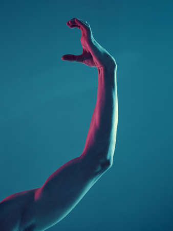 Male hand in graceful gesture on neon blue light background. Concept photography, music or dancing poster Banque d'images