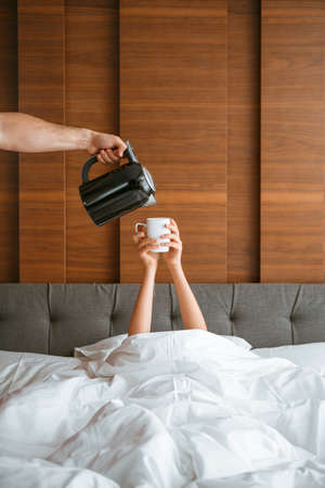 Teen girl under blanket in white bed in bedroom woken up and tea is being poured for her. Breakfast in bed, lazy morning Imagens