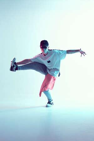 Guy dancing contemporary dance in studio. Neon light blue background. Acrobatic bboy dancer. Break dance lessons.