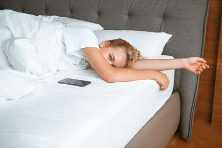 Young girl sleep with phone under blanket in white bed in bedroom. Healthy sleep, healthy sleep apps, lazy morning