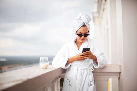 Young cute girl blogger in white robe, towel and sunglasses stands on balcony with phone and cup of milk. Lazy morning