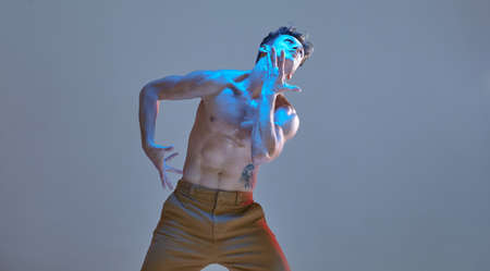 Cool young guy dancing expressive dance without shirt in neon light. Dance school poster. Body with tattoos. Stock Photo