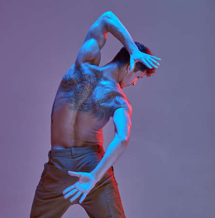 Cool guy dancer without shirt in neon light. Colorful dance school poster. Body with tattoos. View from back