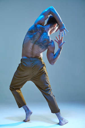 Cool young man in expressive dance without shirt in neon light. Dance school poster. Body with tattoos. View from back Stock Photo