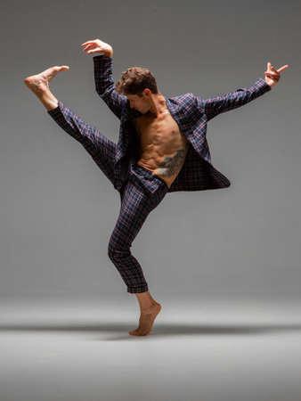 Cool young man dancer dancing expressive dance in suit in studio. Dance school poster. Dance lessons Stok Fotoğraf