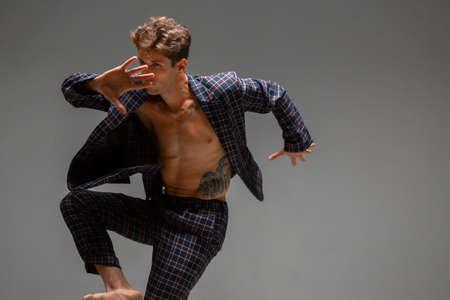 Cool young guy dancer in suit dancing modern expressive dance in studio. Dance school poster. Dance lessons