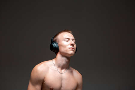 Cool young guy dancer in wireless headphones listen to song and dance hip-hop without shirt. Music and dance poster