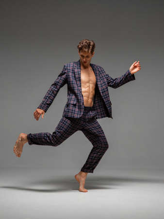 Stylish young man dancer in suit dancing modern dance with torso in studio. Dance school poster. Dance lessons