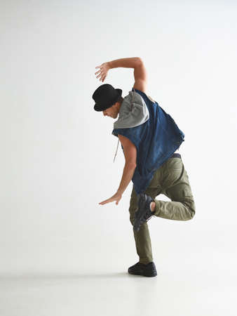 Cool guy breakdancer in hat dancing hip-hop in studio isolated on white background. Break dance lessons. View from back