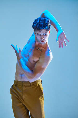 Cool young guy dancing expressive dance without shirt in blue neon light. Colorful dance school poster
