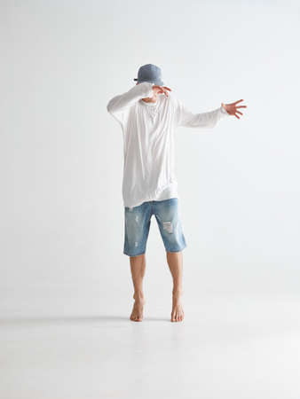 Stylish young guy breakdancer in cap covering face with hands stands on tiptoes barefoot in studio on white background