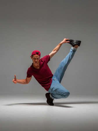 Cool guy breakdancer dancing lower break dance isolated on gray background. Break dance lessons Stok Fotoğraf