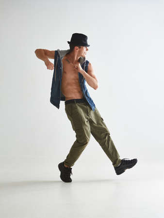 Cool young man breakdancer in hat dancing hip-hop in studio isolated on white background Stok Fotoğraf
